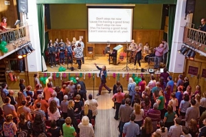 The congregation sings along, karaoke-style, to pop songs rather than hymns at Sunday Assembly, Conway Hall, London